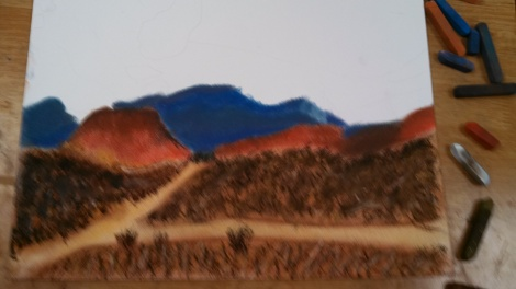 Using hard pastels and straight lines, I added the bushes and scrub to the hills.